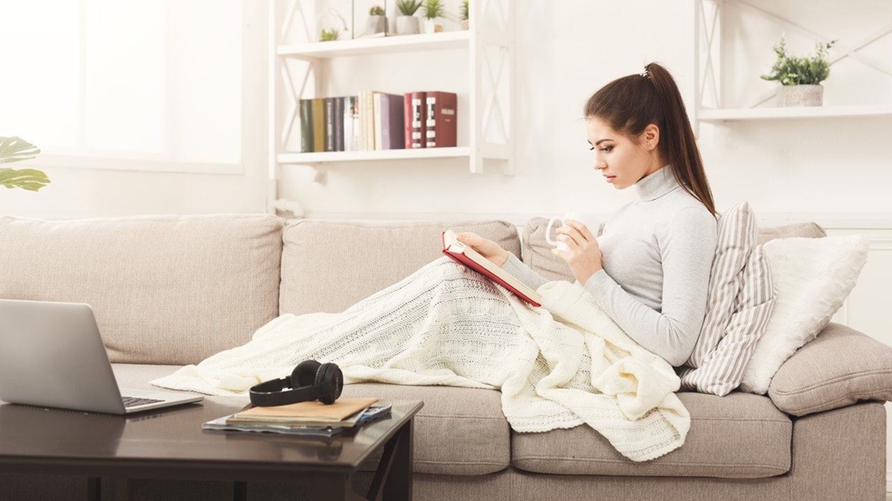 Image of a college student snuggled up on a sofa reading with a coffee cup - dorm alternatives - college apartments in lafayette la