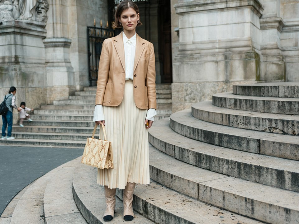 Fall clothing fashion - young professional in shades of cream, long pleated cream skirt, creal long sleeve top, leather jacket in light camel color with ankle books to match - Luxury apartments in lafayette la