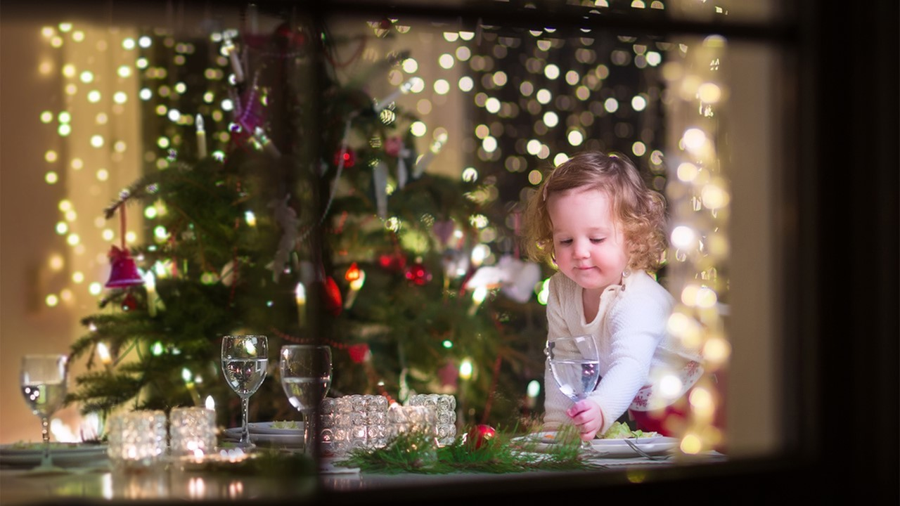 Image of a small child surrounded by Christmas lights reaching for a drink on a table decorated with candles and glassware - two bedroom handicap apartments in lafayette la