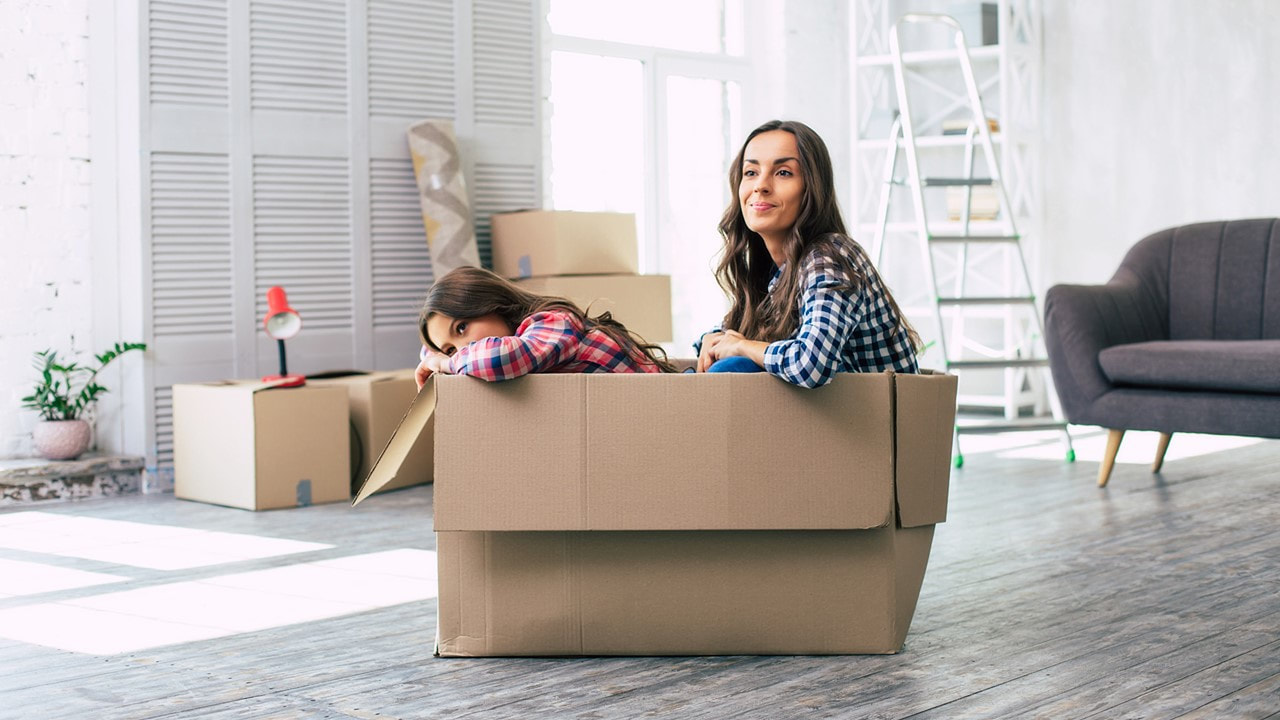image of a woman and her daughter sitting inside a moving box in an fairly empty room - 1 and 2 bedroom apartments in lafayette la