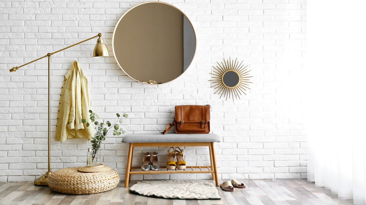 Image of beautiful function entry way, brick wall, round mirror, bench with shoe rack below, hook on the wall and floor lamp - Lafayette Apartments - Lafayette Gardens Apartments